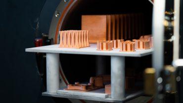 3d-printade föremål i koppar utanför en sintringsugn.